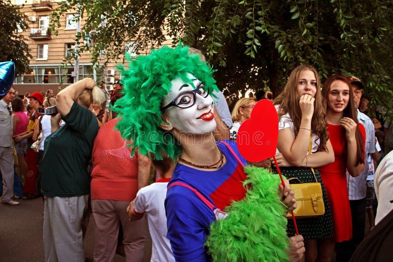 Payaso de sexo femenino en peluca verde y con el corazón en un palillo en el desfile del ` de la cabalgata del circo del ` de los fotos de archivo libres de regalías