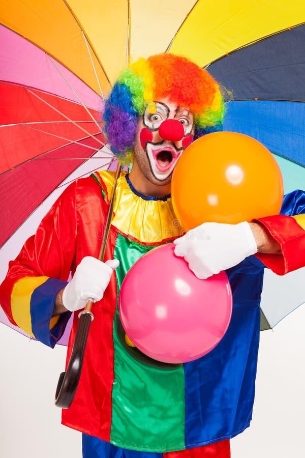 Payaso divertido colorido que sostiene bolas imagen de archivo libre de regalías