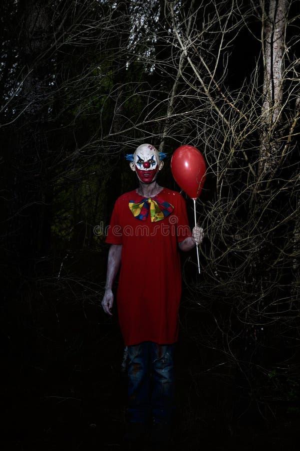 Payaso malvado asustadizo en el bosque en la noche fotografía de archivo