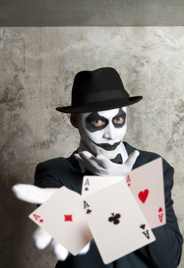 Payaso malvado que juega con las tarjetas del póker imagen de archivo