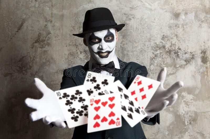 Payaso malvado que juega con las tarjetas del póker imagen de archivo libre de regalías