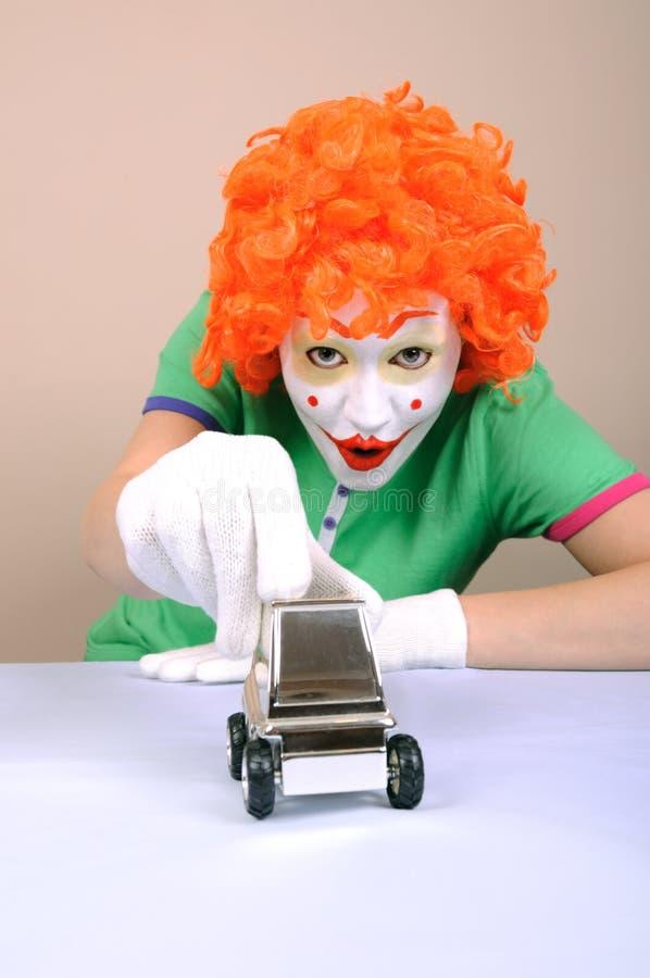 Payaso que juega con el coche del juguete foto de archivo