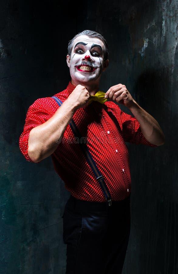 Payaso terrible y tema de Halloween: Payaso rojo loco en una camisa con las ligas imágenes de archivo libres de regalías