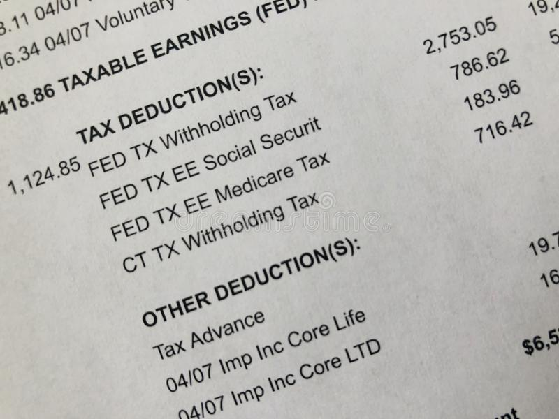 Paycheck tax deduction detail. Close up of a paper paystub showing tax withholding detail stock photography