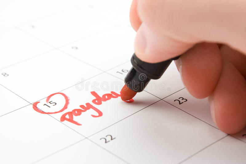 Payday. Hand write payday in to calendar (lead a hand-to-mouth existence stock photography