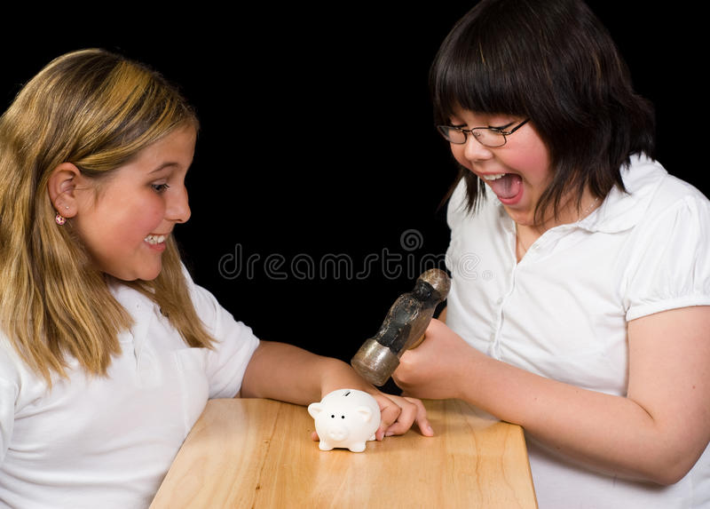 Payday. Two children using a hammer to break open a small piggy bank, shot against a black background stock image