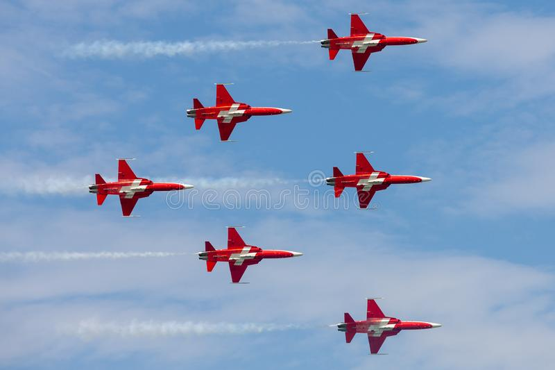Patrouille Suisse formation display team of the Swiss Air Force flying Northrop F-5E fighter aircraft joined by the Swiss PC-7 tea royalty free stock photo