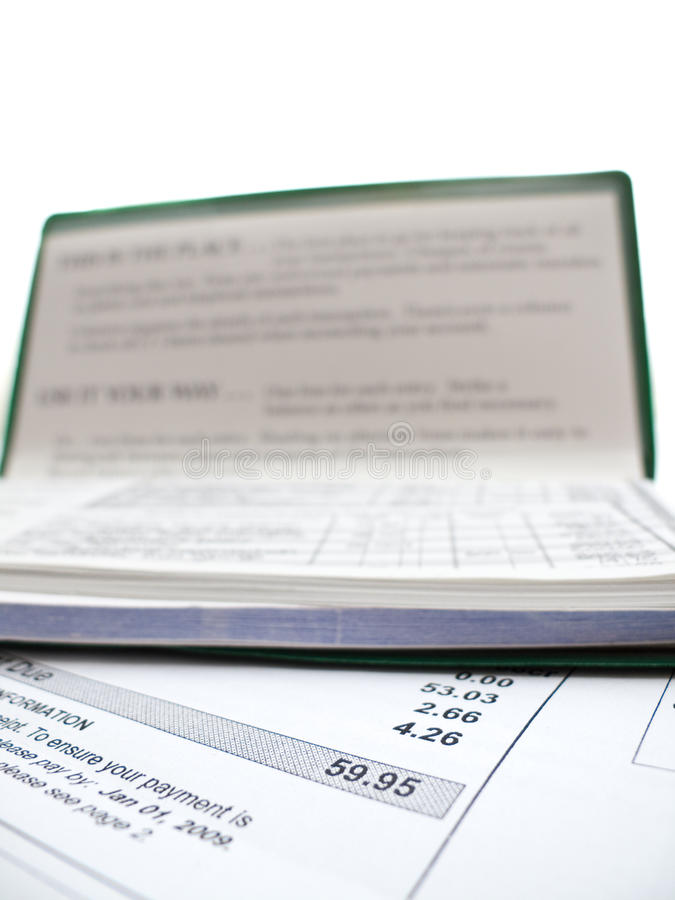 Paying the bills. A cheque book sitting on top of a bill, isolated on white stock photos