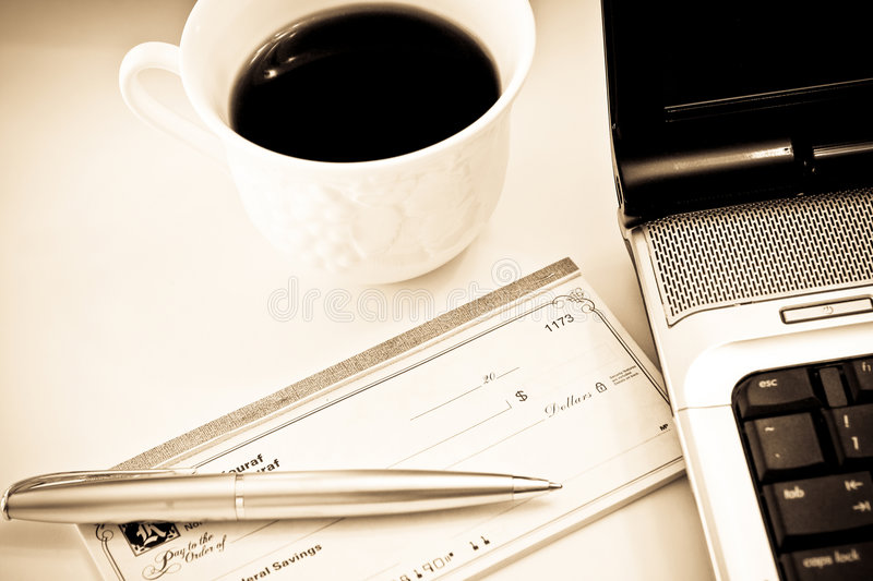 Paying bills. An images of a checkbook with a laptop and coffee in the background stock image