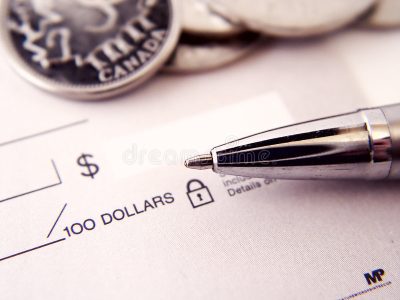 Paying the Bills. With pen and money on blank check book royalty free stock image