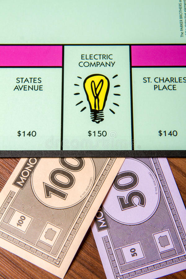 Paying the bills. CALDWELL, IDAHO/USA - MARCH 16, 2015: High priced utilities in the board game monopoly royalty free stock photography