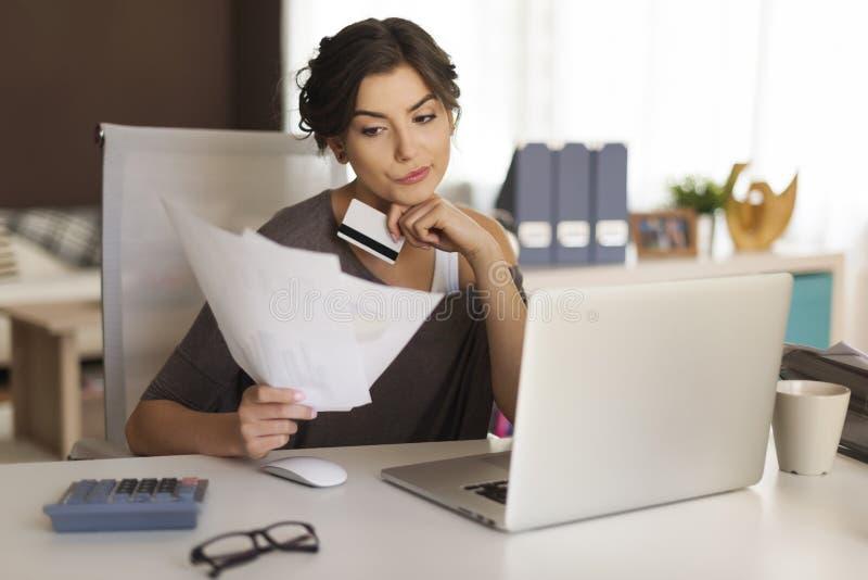 Paying bills by credit card. Pensive woman paying bills at home royalty free stock photo