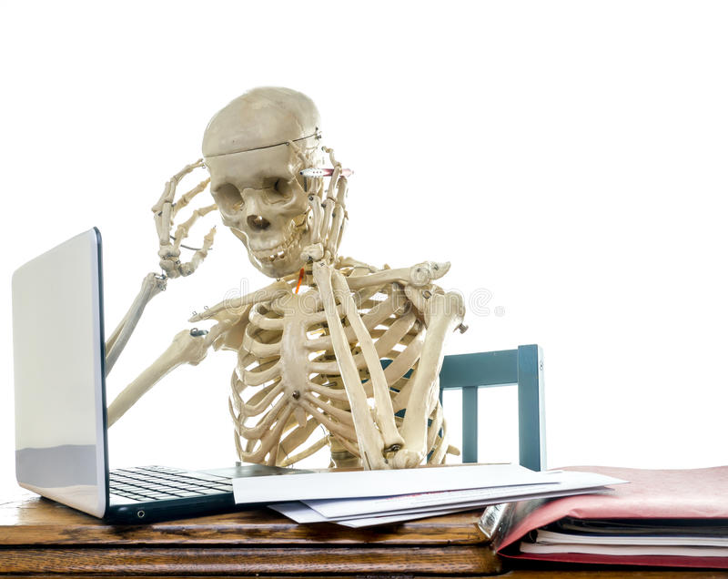 Paying Bills Headache. A human skeleton gets a headache from annoying bill paying royalty free stock image