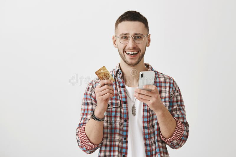 Paying bills with new app is ridiculously easy. Portrait of emotive and excited handsome man in glasses holding credit royalty free stock photography