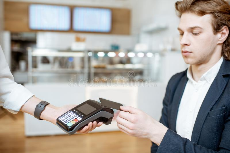 Paying with card at the cafe. Businessman paying contactless with bank card at the cafe royalty free stock images