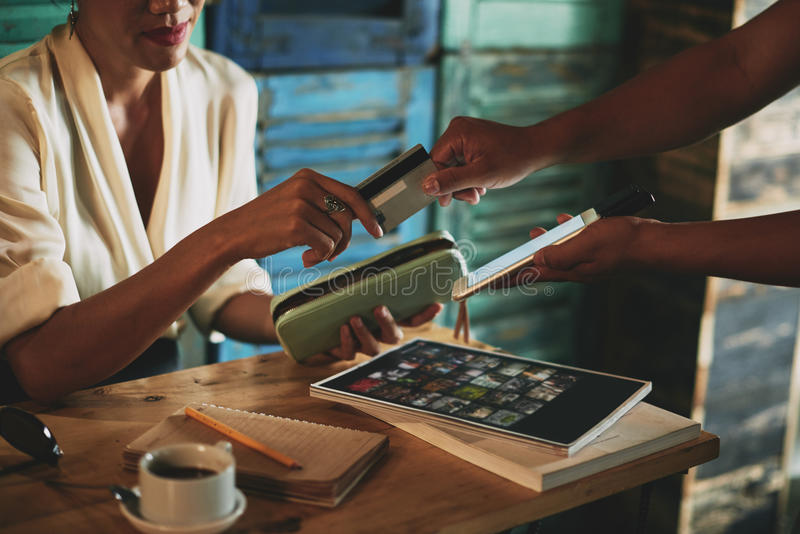 Paying with card. Woman giving credit card to waiter in cafe royalty free stock photos