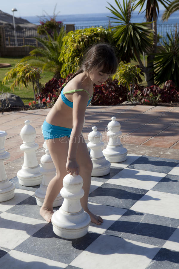 Paying chess. Young girl playing a game of chess with large pieces royalty free stock image
