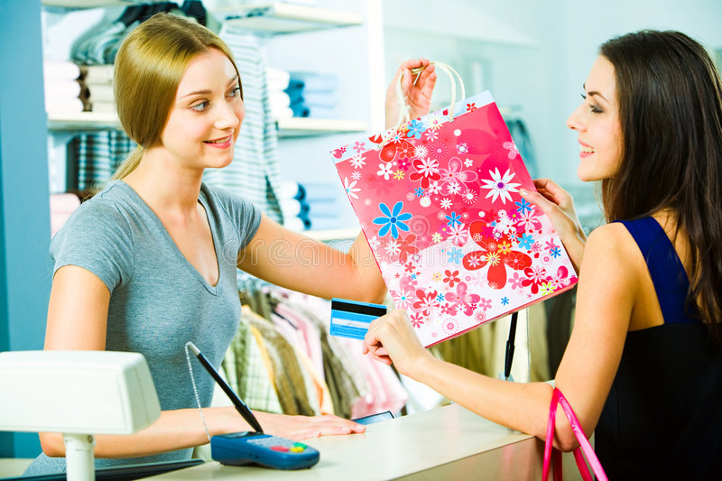 Paying for clothes. Photo of a friendly salesperson giving shopping bag to pretty customer in the mall with smile stock images