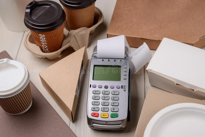Paying for coffee and food. Paying for coffee and take-away food. Terminal printing a receipt after payment. Convenient payments for small restaurant business stock photo