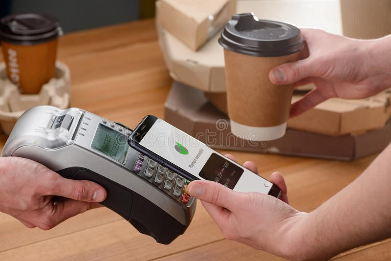 Paying for coffee. By a tap with a mobile phone. Drinks on-the go, city lifestyle and easy contactless payments stock photo
