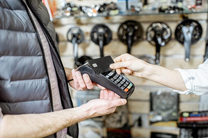 Paying with card at the bicycle shop. Paying contactless with card at the bicycle shop, close-up view stock photo