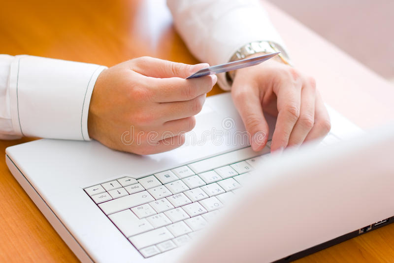 Paying with credit card. Young man paying with a credit card. Shallow focus stock photo