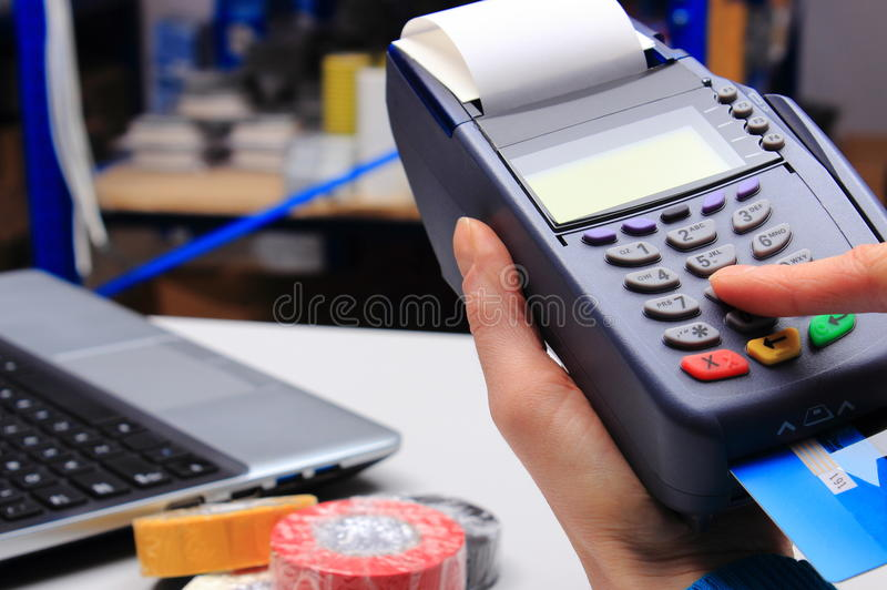 Paying with credit card in an electrical shop, finance concept. Hand of woman using payment terminal in an electrical shop, paying with credit card, credit card royalty free stock images