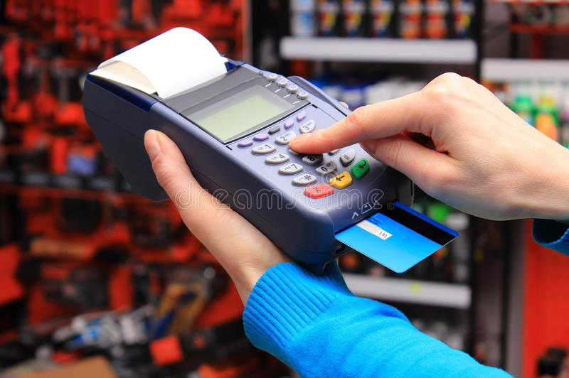 Paying with credit card in an electrical shop, finance concept. Hand of woman using payment terminal in an electrical shop, paying with credit card, credit card stock photos