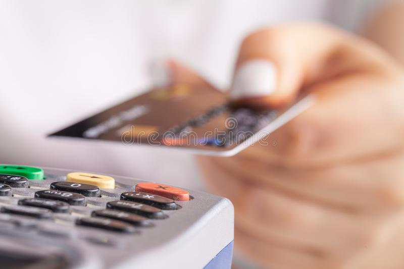Paying with credit card. Female inserting chip card into payment terminal device stock photo