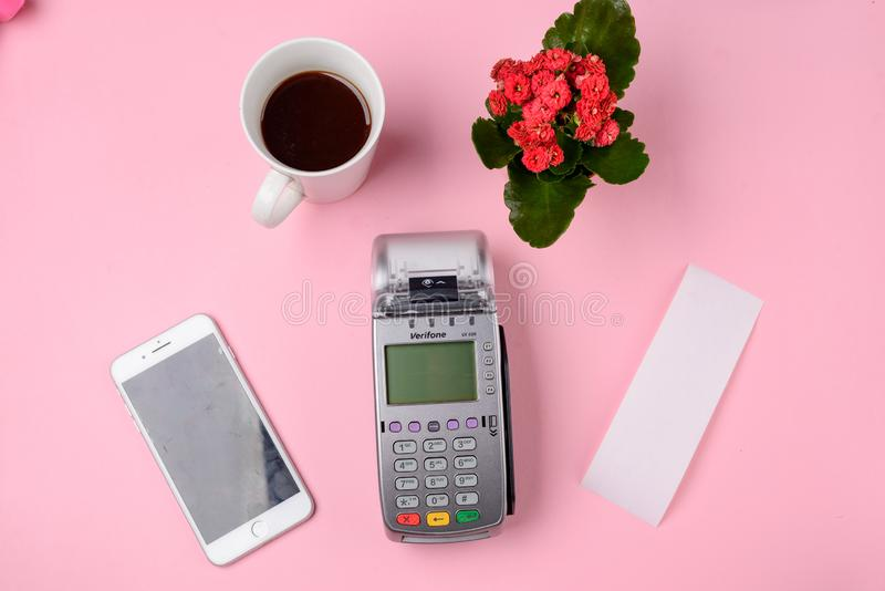 Paying for cup of coffee. Paying for a cup of coffee with a phone and payment terminal. Beautiful pink cafe flat lay stock image