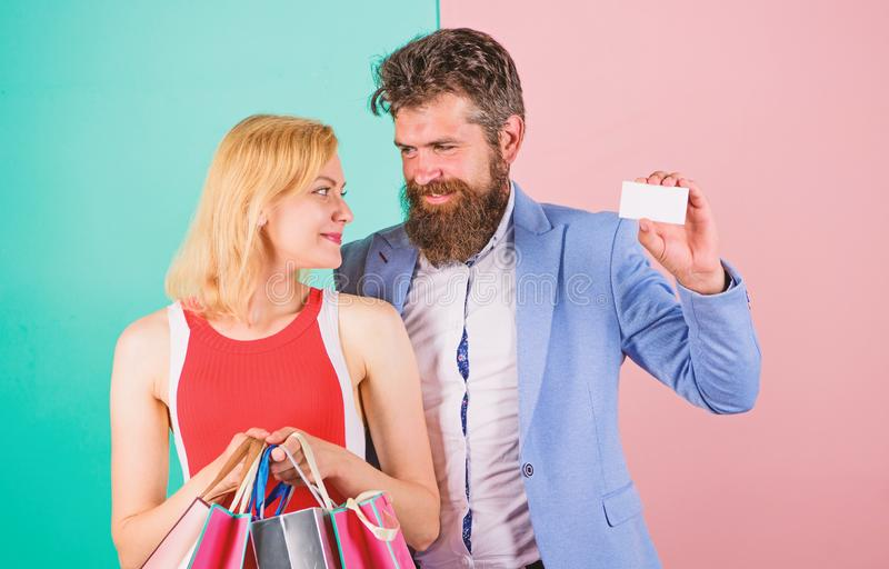 Paying while dating. Couple with luxury bags in shopping mall. Man bearded hipster hold credit card and girl enjoy. Shopping. Ask men to purchase lots presents stock photography