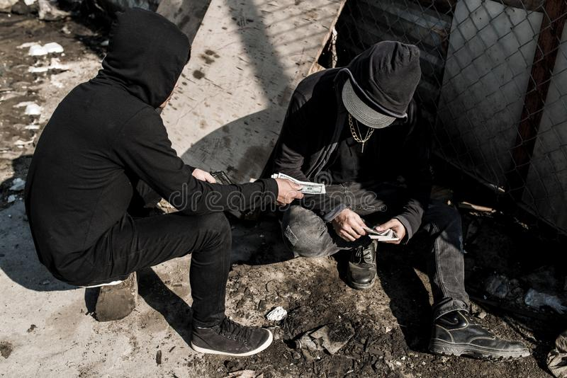 Paying dealer. Addicted men paying dealer for dose of drugs with cash stock image