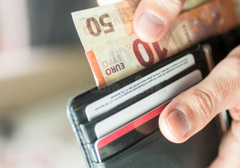 Paying with Euro bank notes from a black wallet. Close-up showing hands paying 60 Euro from a black wallet stock photography