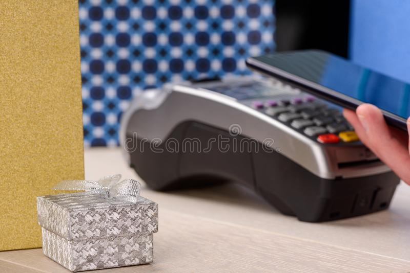 Paying for gifts with phone. Paying for gifts with a phone. Little gift box with jewelry and credit card machine, selective focus royalty free stock images
