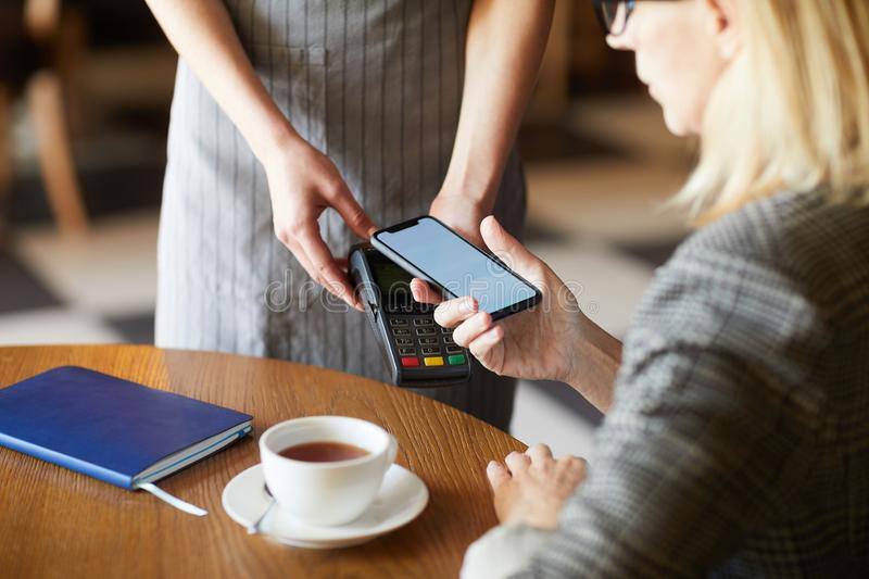 Paying by mobile app. Contemporary mobile businesswoman with smartphone paying by mobile app for her drink and food in cafe or restaurant royalty free stock photography