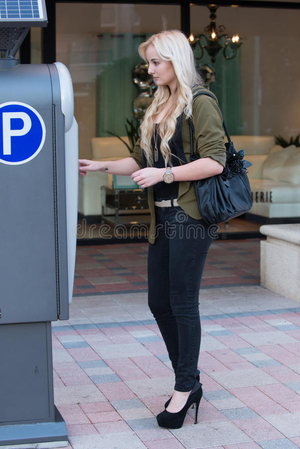 Paying at a parking meter. Young woman model paying interfacing with a parking meter royalty free stock photography