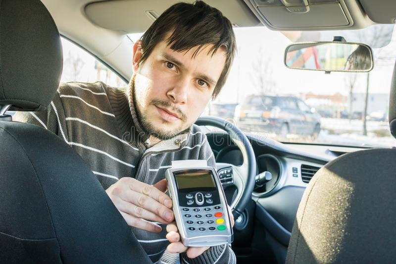 Paying for transportation. Taxi driver is offering payment terminal to customer.  royalty free stock photography