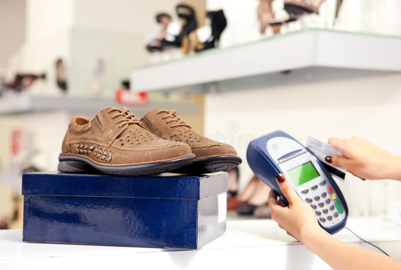 Paying using credit card terminal in shoe store. Moment of payment using credit card terminal in shoe store. Selective focus on pair of male shoes on top of box stock photography