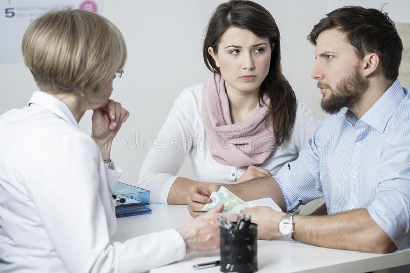 Paying for visit. Young worried couple paying to experienced doctor for visit royalty free stock image