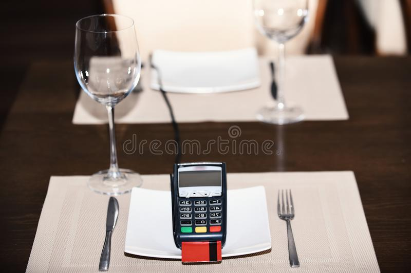 Payment with credit card. Credit card terminal on plate royalty free stock image
