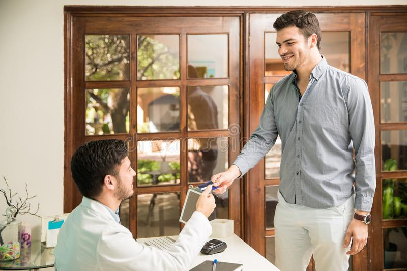 Payment for health services at a spa. Attractive young men using a credit card to pay for some health services in a wellness and spa clinic royalty free stock images