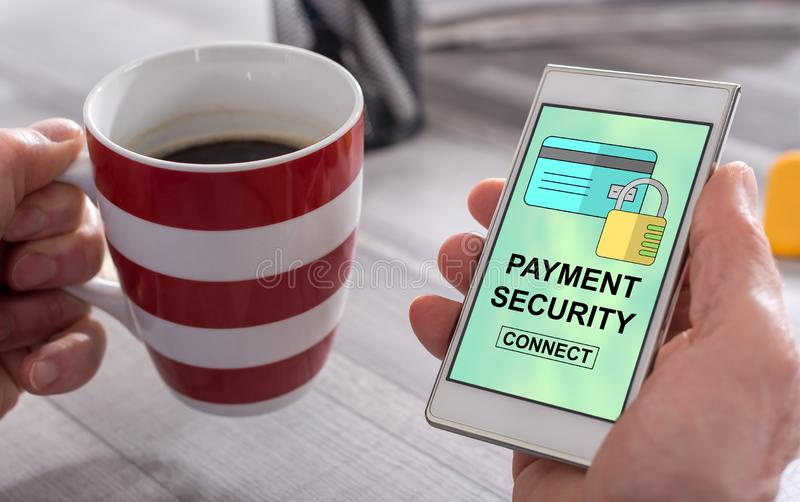 Payment security concept on a smartphone. Male hand holding a smartphone with payment security concept stock photo