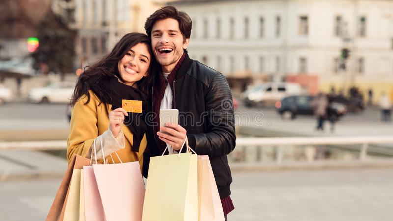 Payment and shopping online. Couple with credit card and bags. Outdoors, copy space stock image
