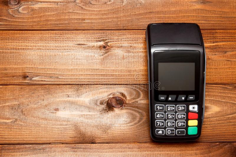 Payment terminal, compact POS terminal on wooden background top view copy space royalty free stock images
