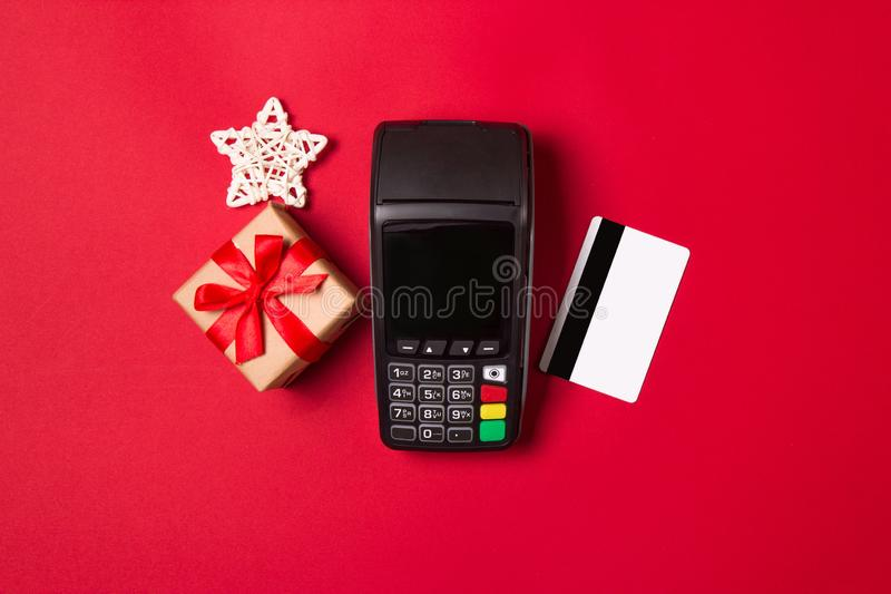 Payment terminal with credit card and gift on a red paper background. Christmas sale concept.  stock photography