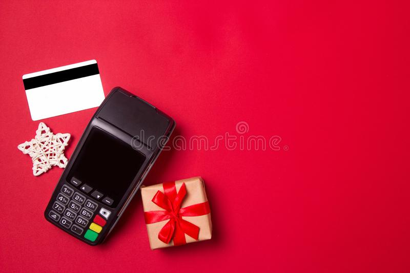 Payment terminal with credit card and gift on a red paper background. Christmas sale concept.  royalty free stock photography