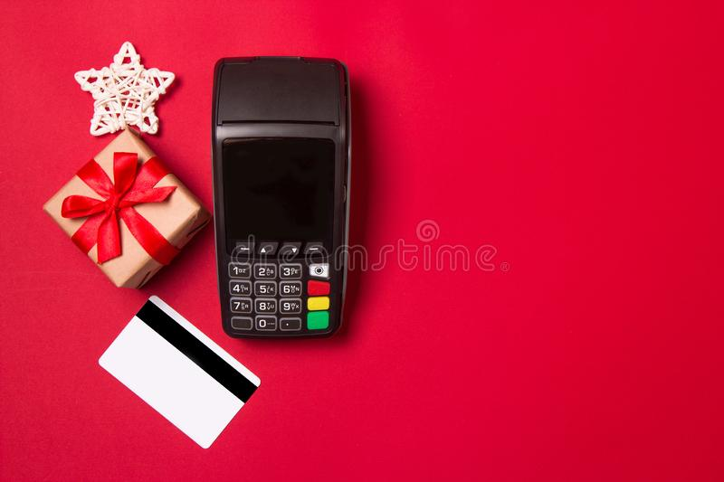 Payment terminal with credit card and gift on a red paper background. Christmas sale concept.  royalty free stock photos