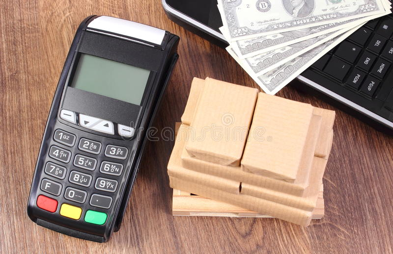 Payment terminal with currencies dollar, laptop and boxes on pallet, paying for shipping and products stock images