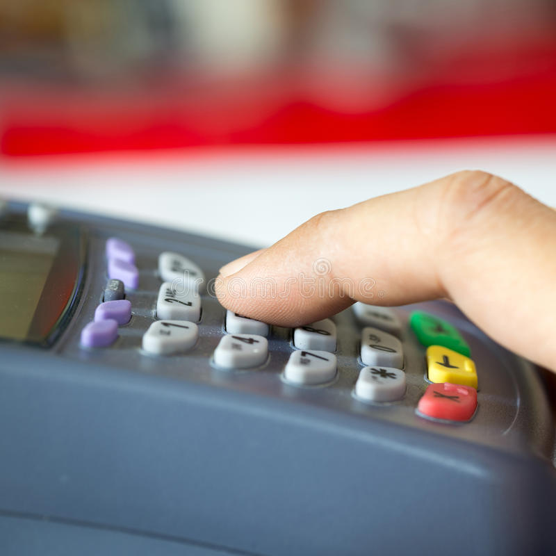 Payment terminal with keypad and a finger pressing on button. Selective Focus stock image