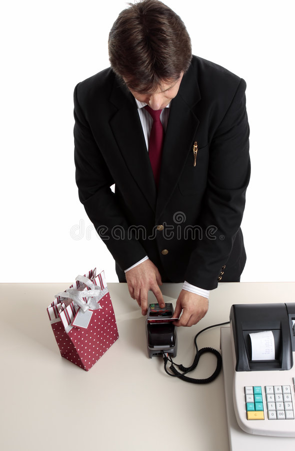 Payment transaction. A consumer enters pin number to make a retail payment transaction for a birthday or Christmas present. Focus to hands royalty free stock photos